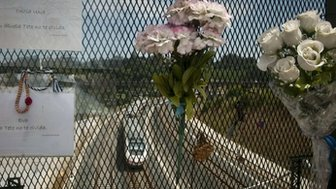 A high-speed train arrives under a bridge where flowers and messages are displayed near Santiago de Compostela on 23 July 2014.