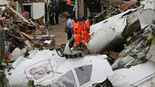 Rescue workers survey the wreckage of TransAsia Airways Flight GE222 on the Taiwanese island of Penghu on 24 July 2014