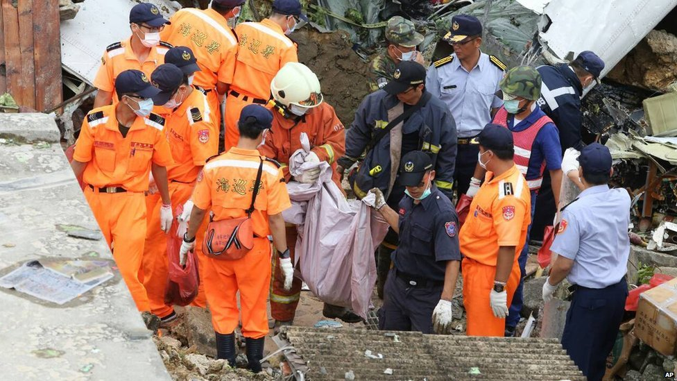 Rescue workers and firefighters search through the wreckage in Penghu on 24 July 2014