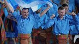 Tartan-clad performers holding the Saltire