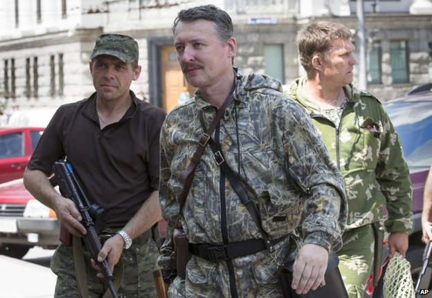 Rebel commander Strelkov, flanked by guards, in Donetsk on 11 July