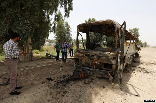 A charred bus at the spot where the ambush took place in Taji, Iraq, 24 July