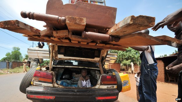 Men check a loaded car, in which trunk a young girl is seated, at an anti-balaka checkpoint in Bangui on 1 March 2014