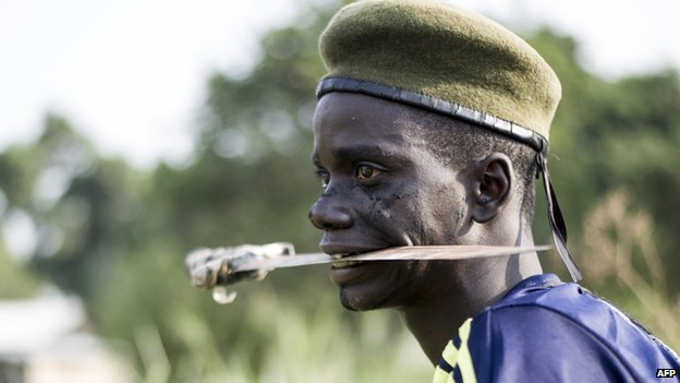 A member of the anti-balaka militia holds a blade in his mouth as he trains in the Boeing neighbourhood of Bangui, Central African Republic, on 24 February 2014