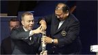Chris Hoy and Prince Imran wrestle with baton
