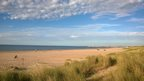 Light blue sky over a quiet beach scene, the sea a deep blue and calmly lapping at the dark yellow sand of the beach. A few people are scattered around and the beach graduates into grass bank in the foreground. Scattered white clouds above.