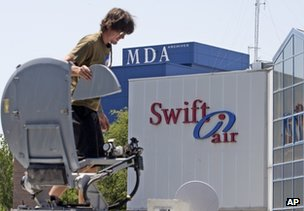 A television camera operator mounts a satellite dish on top of a van outside the Swiftair offices in Madrid, Spain,  24 July