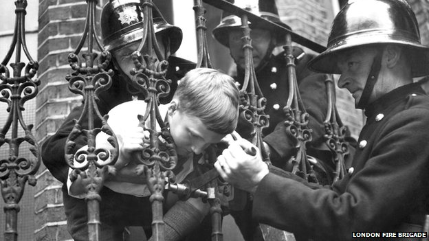 Boy with head stuck in railings