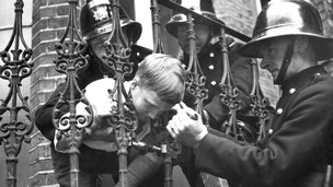 Boy with head stuck in railings
