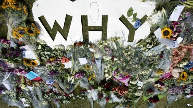 "Flowers in tribute to the victims of flight MH17 are laid around a cutout reading ""Why"", near the entrance to the military airport in Eindhoven, southern Netherlands, 24 July 2014"