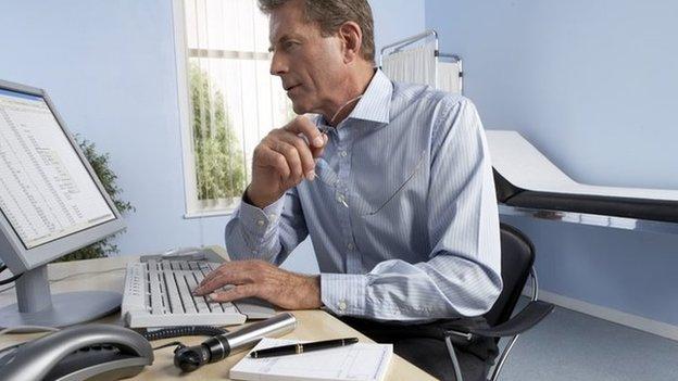 Doctor checks computer screen