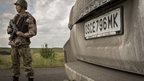 Pro-Russia rebels guard a road leading to wreckage of Malaysia Airlines flight MH17 on 22 July 2014 in Grabovo, Ukraine.