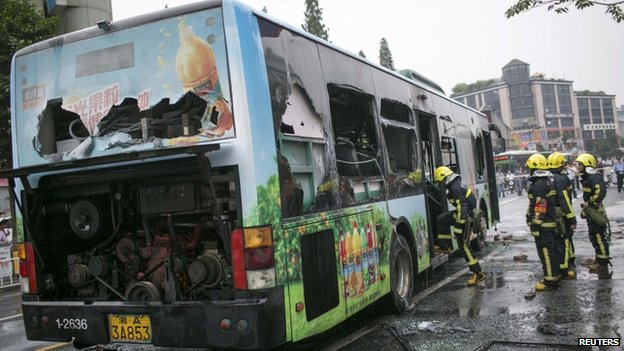 Firefighters inspect a burnt-out bus after putting out the fire on a street in Hangzhou, Zhejiang province on 5 July 2014