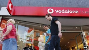 People walk past a Vodafone shop