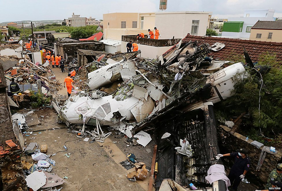 Rescue personnel survey the wreckage of a TransAsia Airways aeroplane