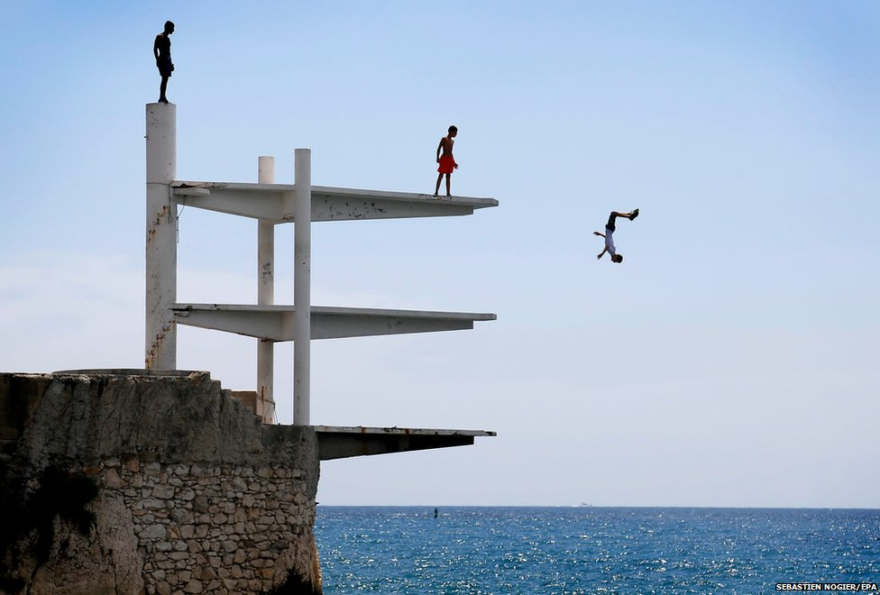 People dive into the Mediterranean Sea on a hot summer's day in Nice, southern France