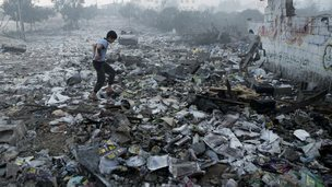 Palestinian boy walks through rubble in Gaza City (24 July 2014)
