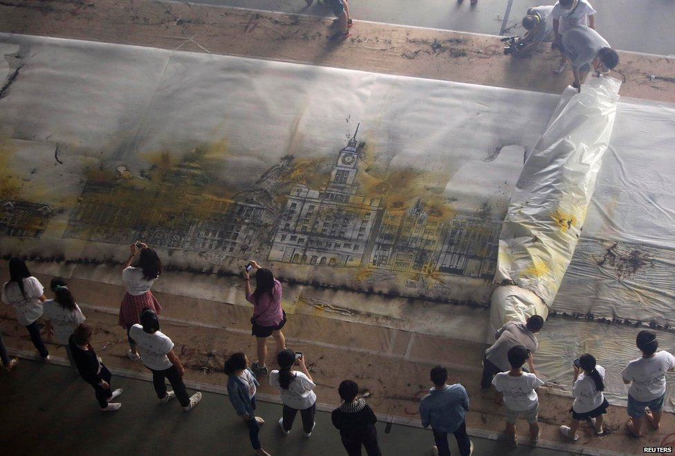 People remove the cover from The Bund Without Us, an artwork made by artist Cai Guoqiang, in Shanghai, China