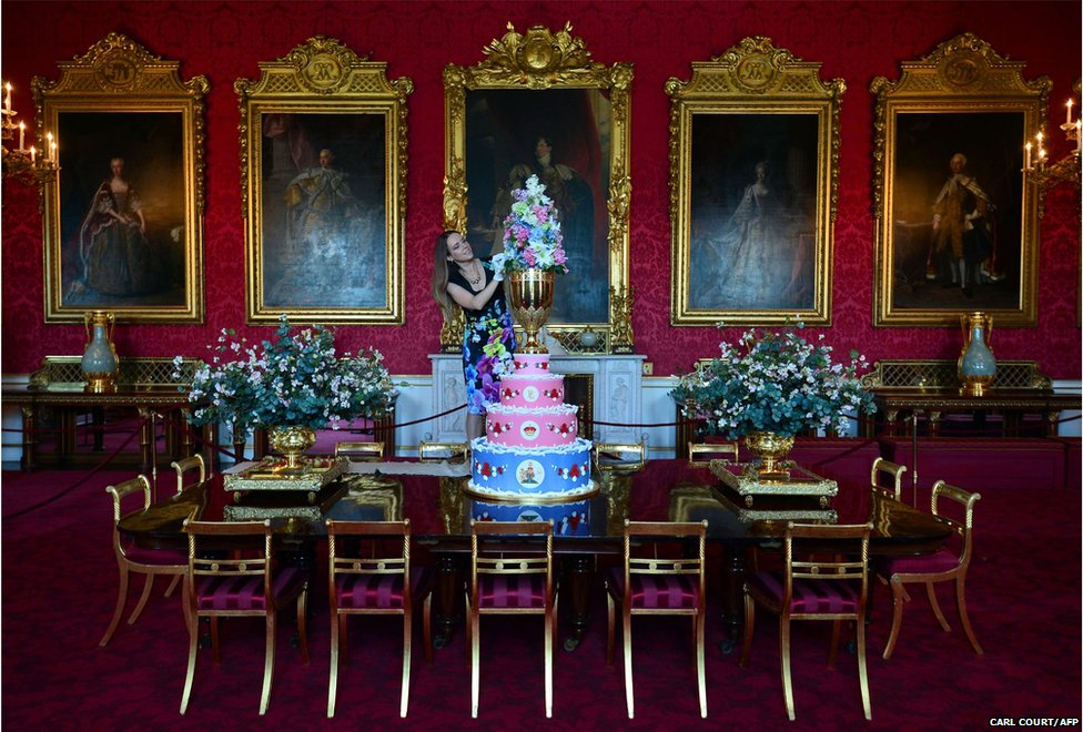A member of staff poses for photographers with a replica of the cake chosen to celebrate the christening of Queen Victoria's youngest son, Prince Leopold, in 1853, at Buckingham Palace in central London