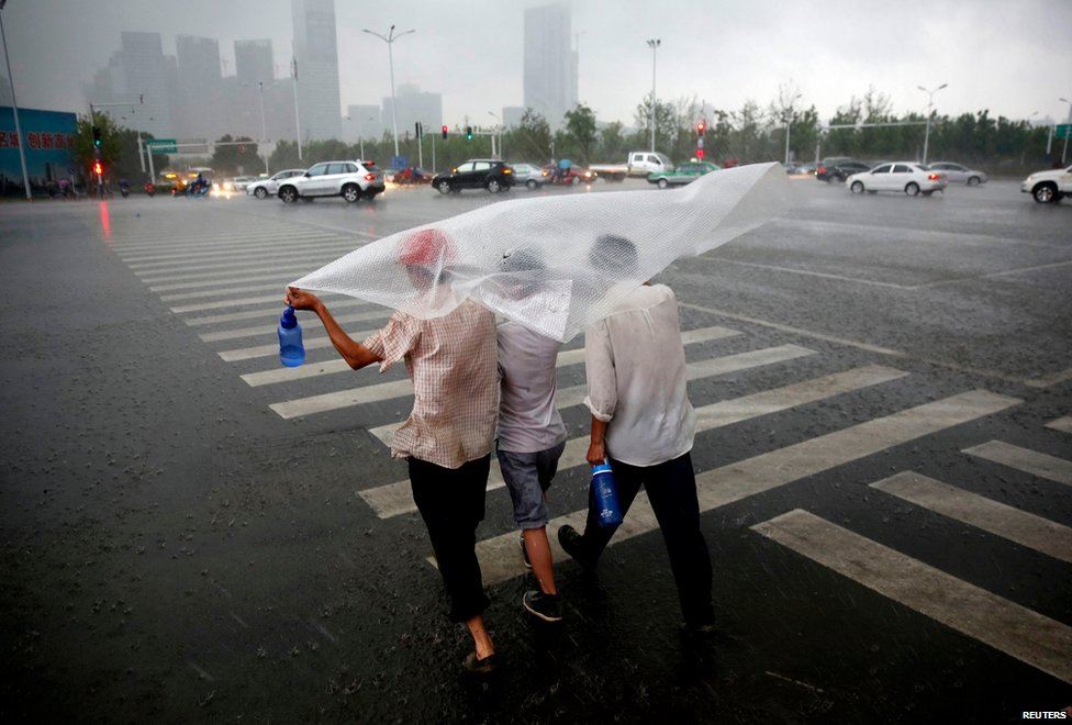People cover themselves with a plastic sheet to shield from strong wind and heavy rainfall as Typhoon Matmo hits Hefei, China