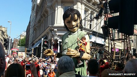 Little Girl Giant giving kids a ride on her arms
