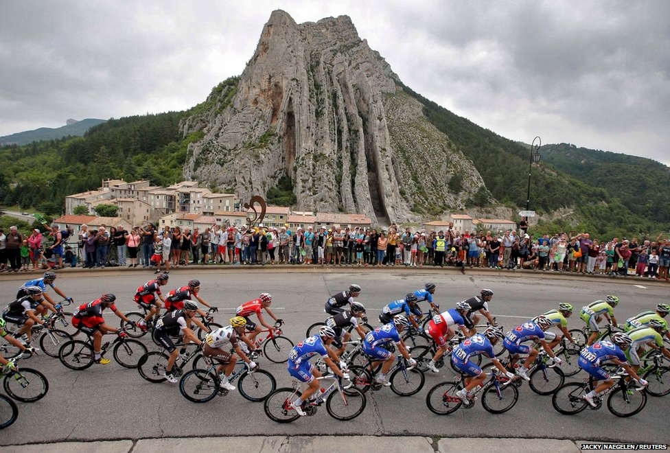 The pack of riders pass a rock formation in Sisteron during the 15th stage of the Tour de France cycle race