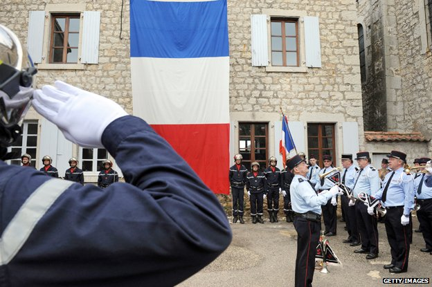 French officer salutes French flag while police and fire workers stand to attention