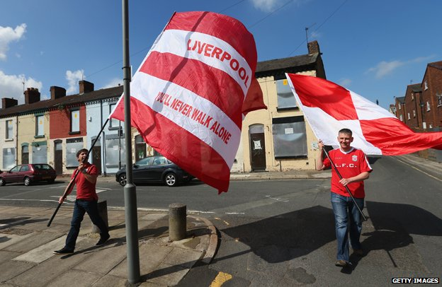 Liverpool fans bear flags proclaiming their allegiance