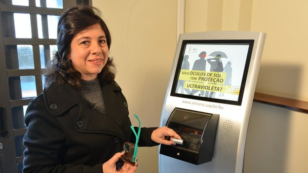 Professor Liliae Ventura stands in front of a kisok-like machine holding a pair of sunglasses