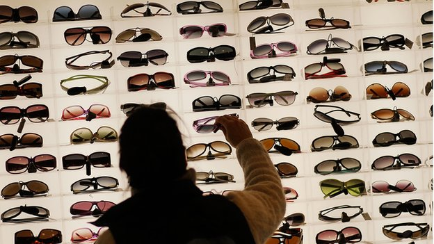 A women stands in front of a large display of sunglasses