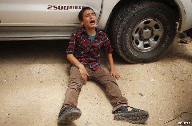 A Palestinian boy whose family was killed weeps at their funeral in Gaza City, 13 July