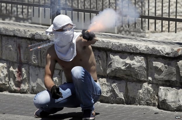 A Palestinian points a flare at Israeli police officers after Friday Prayers in East Jerusalem, 25 July
