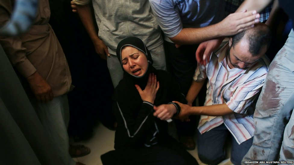 The daughter of Tawfiq al-Aga, who medics said was killed in Israeli shelling, mourns next to her father's body during his funeral in Khan Younis in the southern Gaza Strip