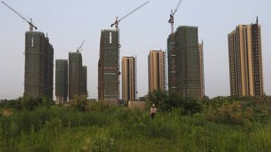 A farmer walks in front of a construction site of new residential buildings in Hangzhou, China