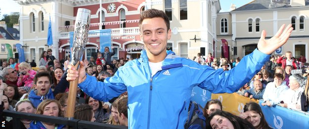 Tom Daley carries the Commonwealth Games Baton as it arrives into St Aubans harbour, Jersey