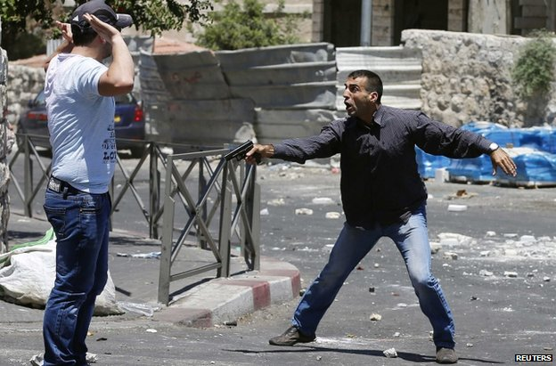 An Israeli plainclothes police officer confronts a suspected Palestinian stone-thrower after Friday Prayers in East Jerusalem, 25 July