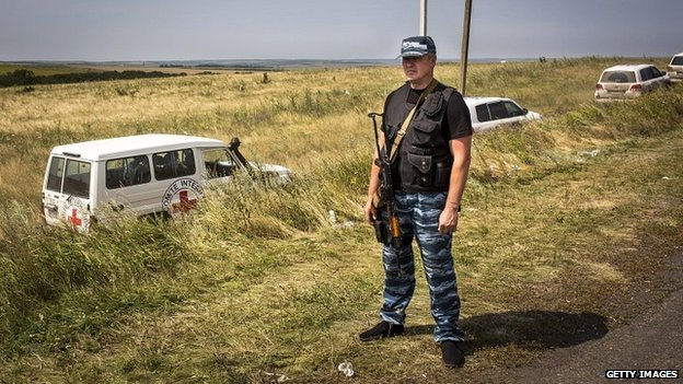 A rebel fighter stands guard at the crash site of MH17 as international observers inspect the area - 24 July 2014