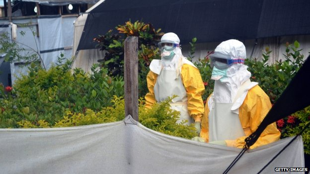 Members of Doctors Without Borders (MSF) wearing protective gear walk outside the isolation ward of the Donka Hospital, on 23 July 2014 in Conakry
