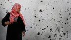 A woman in Gaza looks at adamaged wall in Beit Hanoun, 26 July 2014