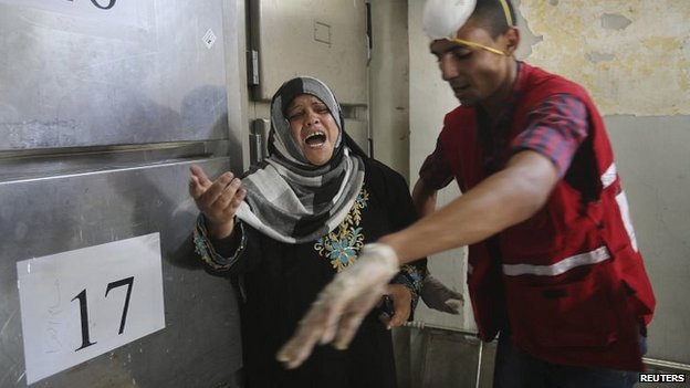 A woman weeps at the morgue in Khan Younis after a strike on a family home killed a reported 19 people (26 July 2014)