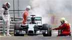 Lewis Hamilton looks at his Mercedes while marshals put a fire out