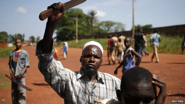 A man holds up a knife during a protest against French peacekeeping troops in Bambari on 23 May 2014.
