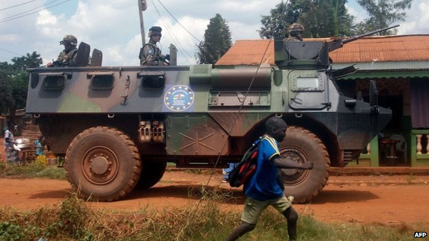 French Sangaris troops patrol in an armoured personnel carrier (APC) as a schoolboy passes by, in Bangui, the Central African capital, on 13 July 2014.