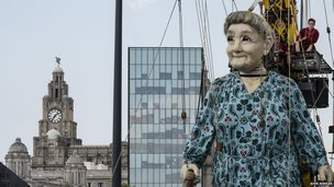 Grandma Giant makes her way along the Strand, Liverpool with the Liver Buildings in the background.