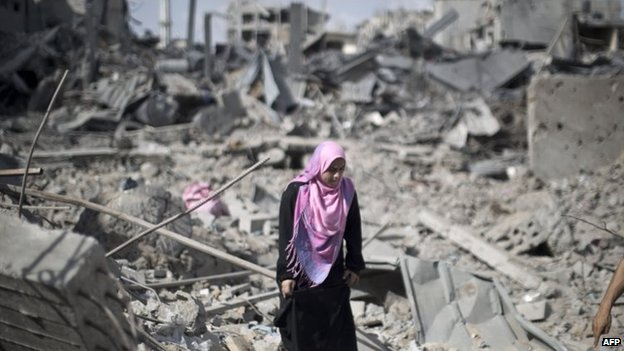 A Palestinian woman walks across the rubble of destroyed buildings and homes in the Shejaiya residential district of Gaza