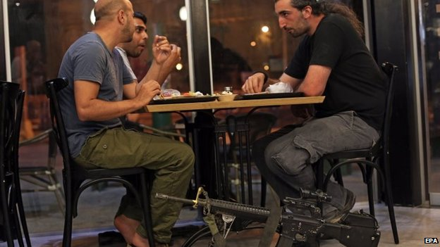 Israeli reserve soldiers eat at a local restaurant at the southern Israeli town of Sderot