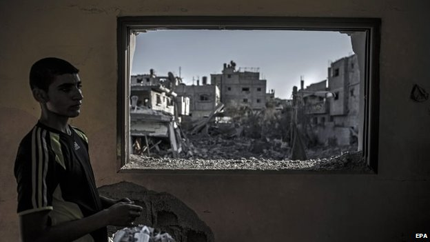 A young Palestinian man stands in his bedroom which was hit by an Israeli tank shell
