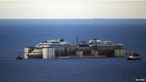 Tug boats tow the Costa Concordia cruise liner as they arrive outside a port near Genoa in northern Italy, where it will be being broken up for scrap, on 27 July 2014.