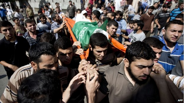 People carry the body of a killed Palestinian in northern Gaza (27 July 2014)