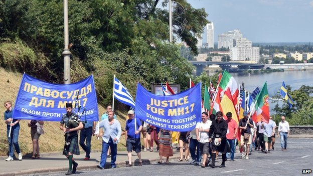 Diplomats and employees of embassies and foreigners working and living in Ukraine carry flags of their countries and placards during a rally in Kiev on 27 July 2014.